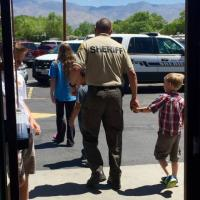Photo showing a police officer holding hands with a kid after shopping
